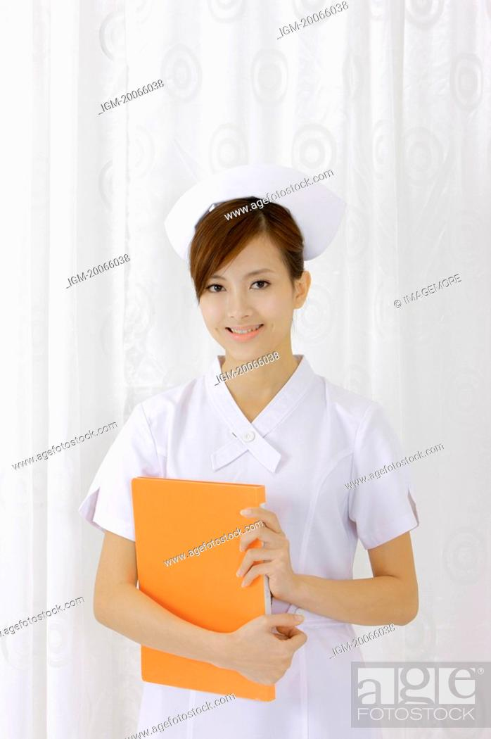 Stock Photo: Young nurse holding document folder and smiling at the camera.