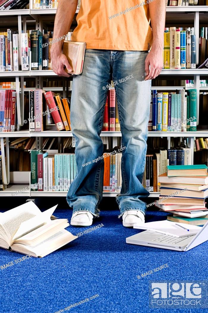 Stock Photo: Student and books in library.