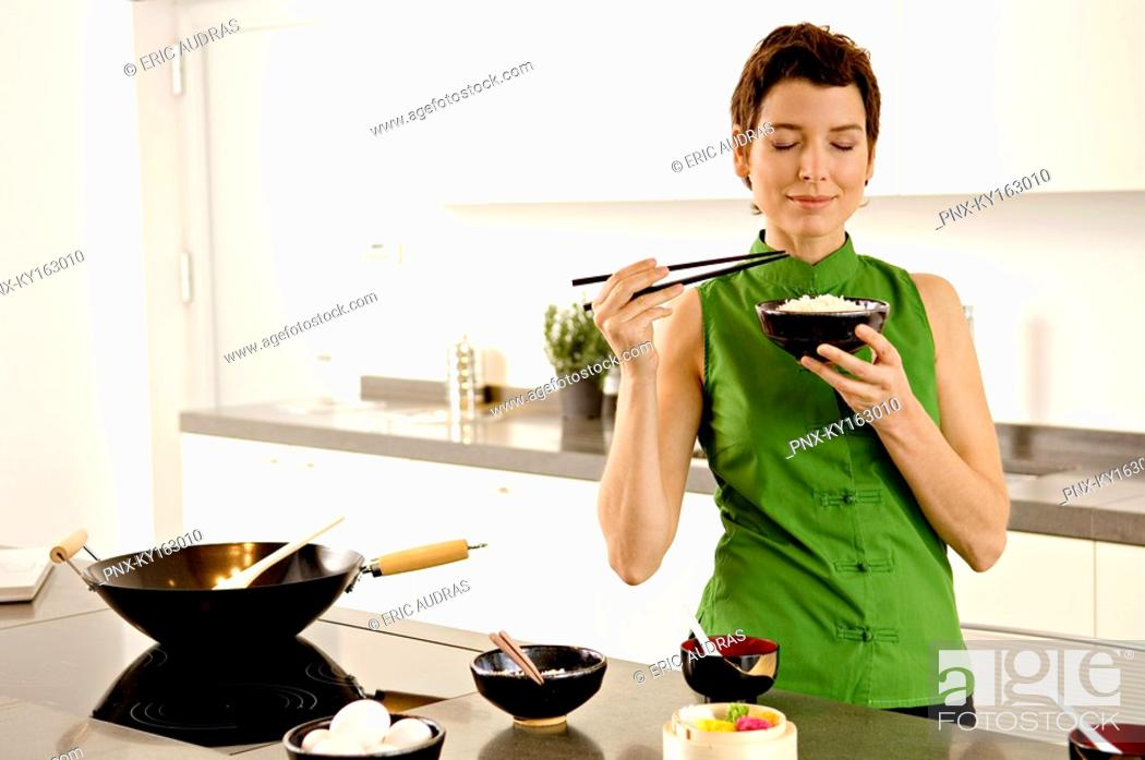 Stock Photo: Mid adult woman smelling a bowl of rice in the kitchen.