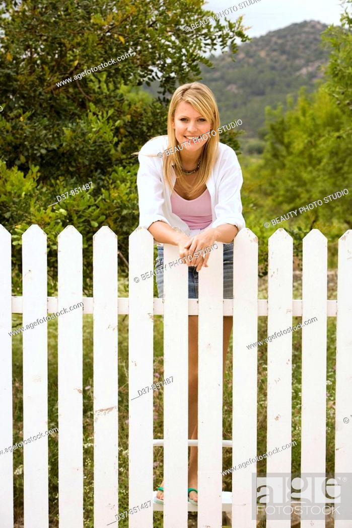Stock Photo: Woman standing behind a fence in the garden.