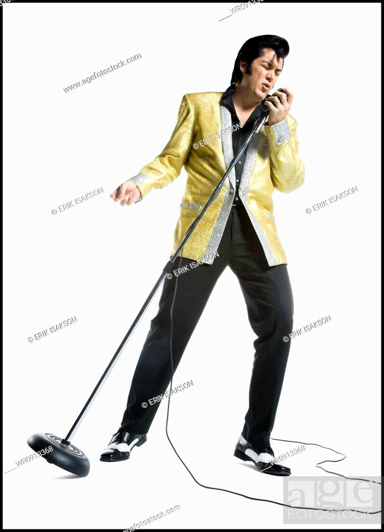 Stock Photo: An Elvis impersonator singing into a microphone.