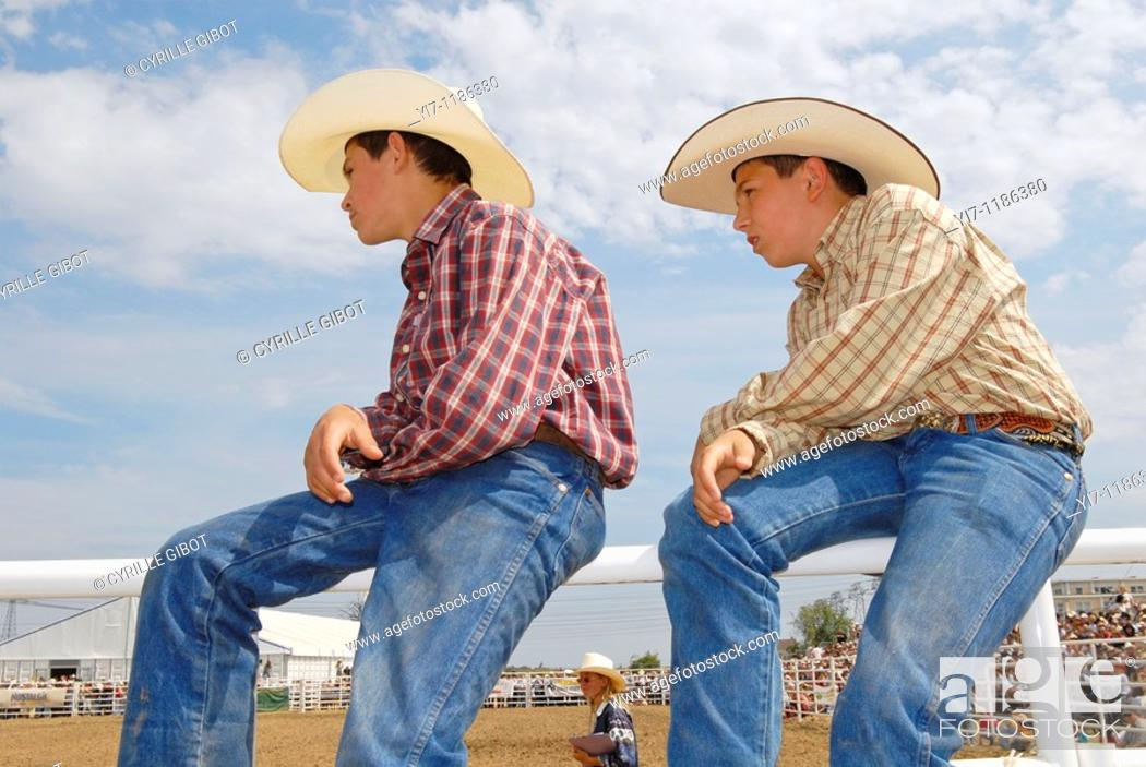 Stock Photo: Two boys in cowboy outfit watching a rodeo.
