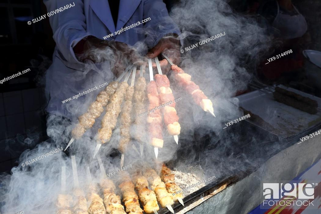 Stock Photo: Tashkent, Uzbekistan - May 01, 2017: Shashlik, a regional Uzbek dish is being prepared by an unknown cook in a traditional styled barbeque at food court.