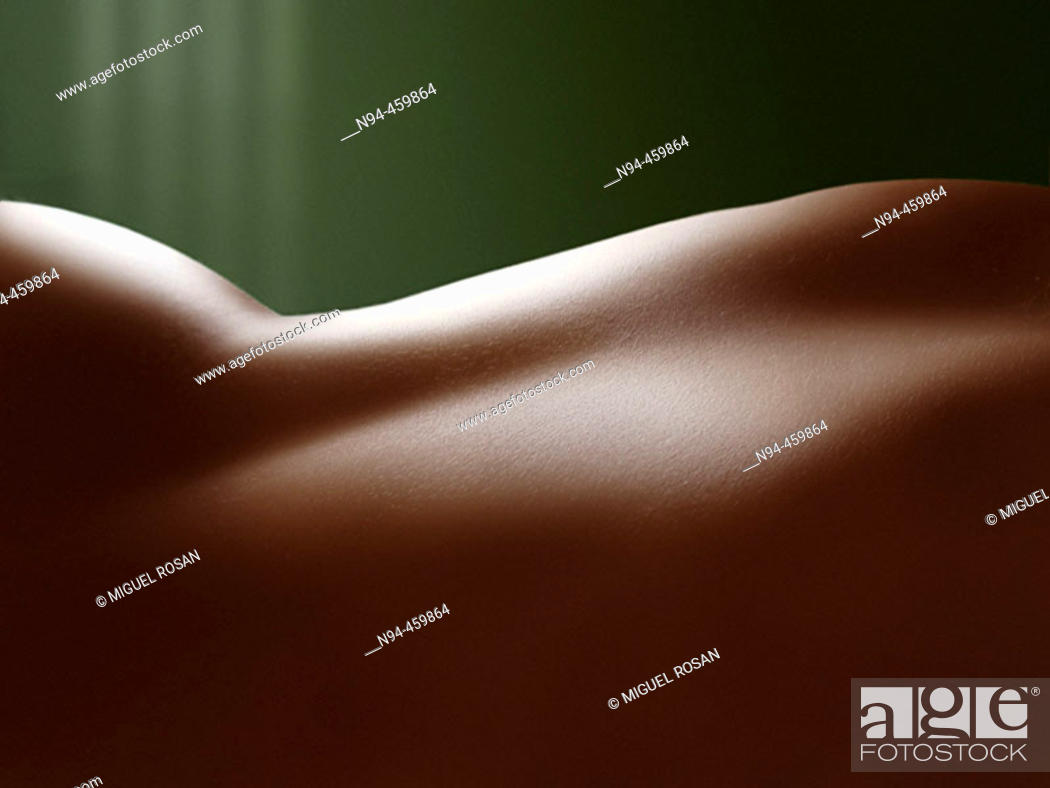 Stock Photo: Female torso lying in the room to the light.
