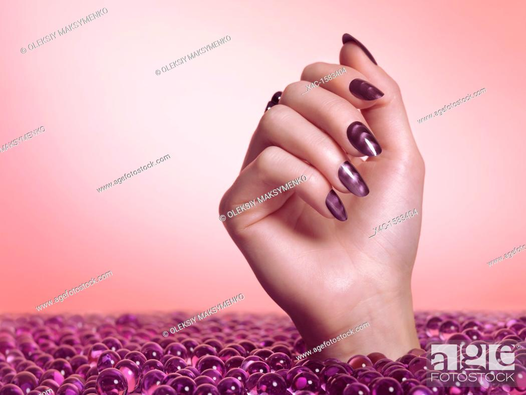 Stock Photo: Woman hand with purple nail polish coming out of a sea of candy on pink background.