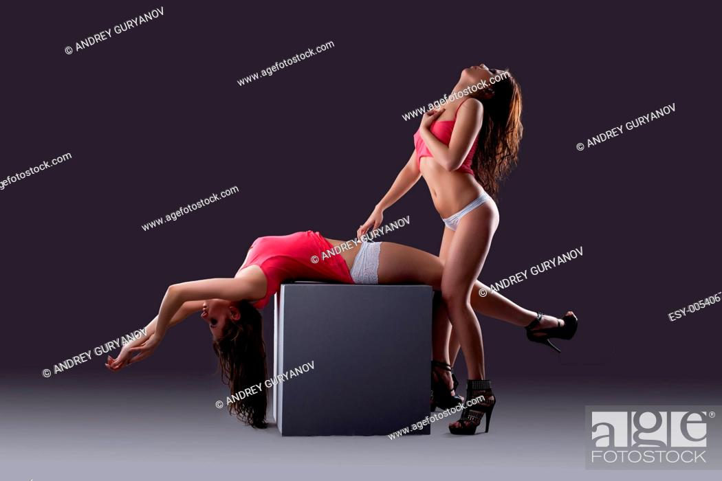 Stock Photo: couple of sexy young woman posing in wet tank top.