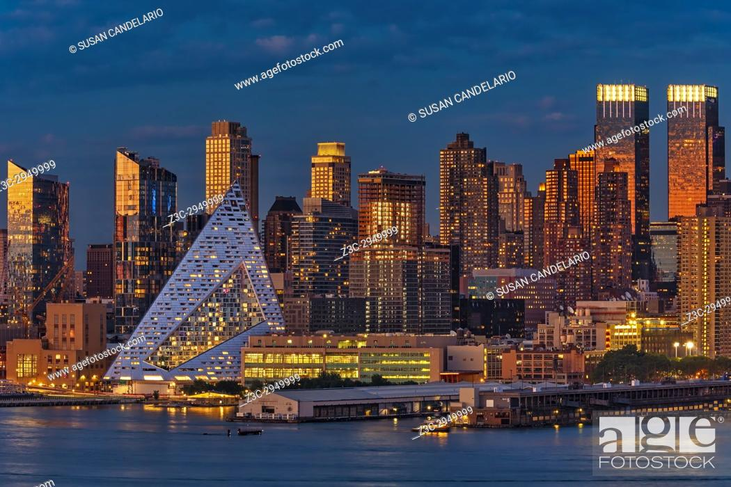 Stock Photo: NYC Golden Empire - The midtown Manhattan New York City skyline is bathed with warm light from the setting sun and cool hues during the blue hour at twilight.