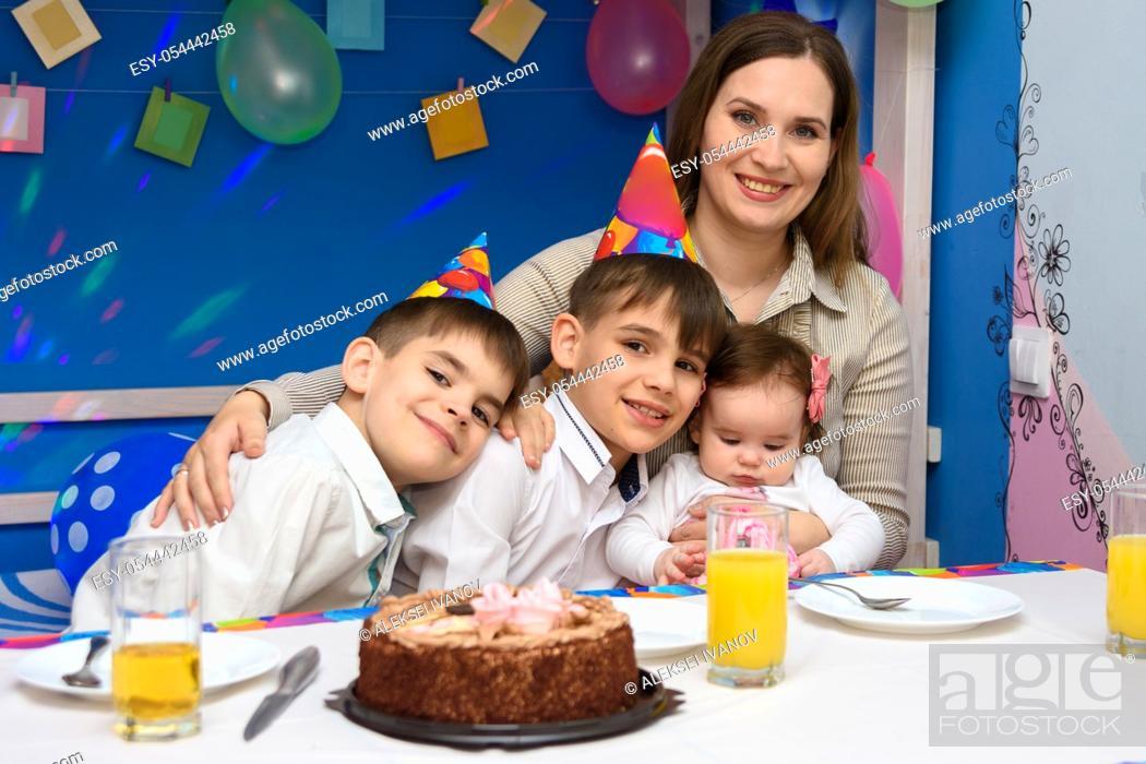 Stock Photo: Happy family hugs mom at birthday party.