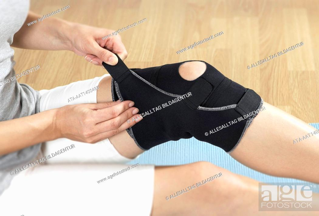 Stock Photo: Woman putting a bandage on her knee.