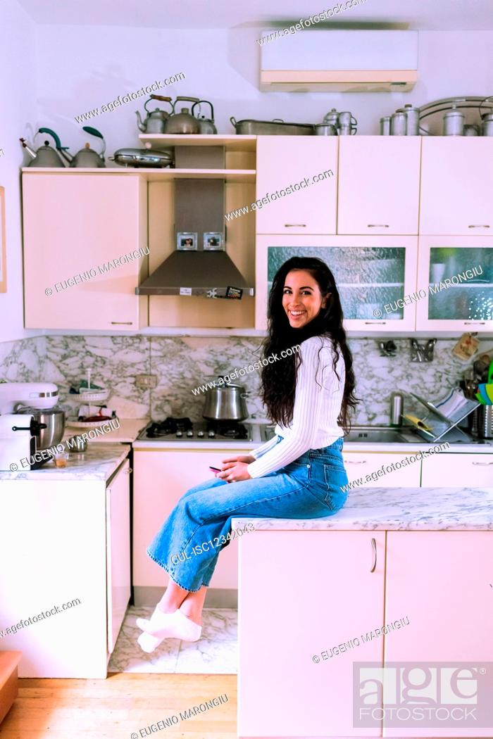 Stock Photo: Young woman sitting on kitchen counter.