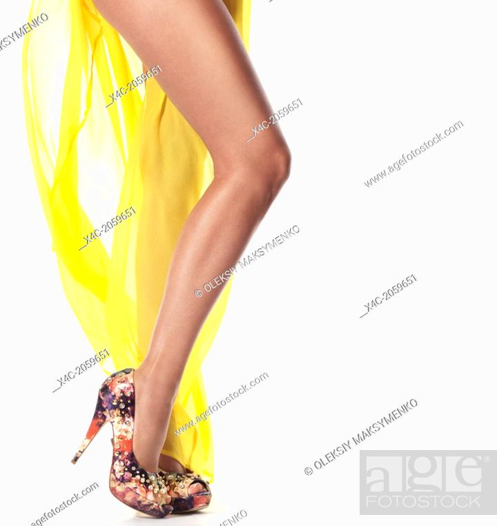 Stock Photo - Sexy long legs of a young woman wearing yellow summer beach  dress and high heel shoes isolated on white background. a48803814c9