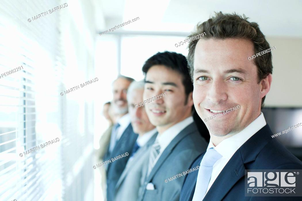 Stock Photo: Portrait of smiling business people standing in a row at window.