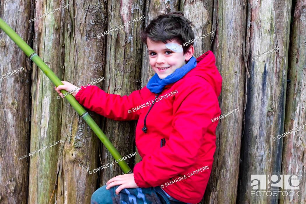 Stock Photo: portrait of smiling 10 year old boy dressed in red jacket, leaning on a bamboo, with wooden planks background.