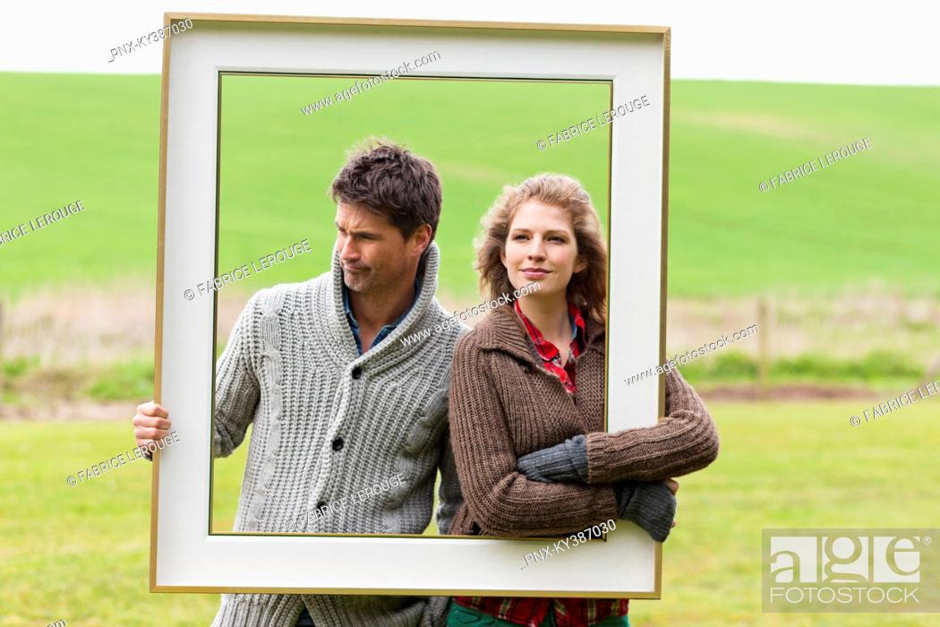 Stock Photo: Couple holding a frame in a field.