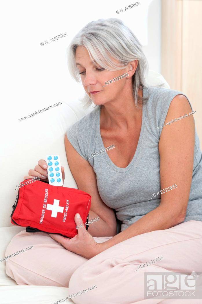 Stock Photo: Beautiful mature woman sitting on her bed and taking tablets out of a red first aid kit.