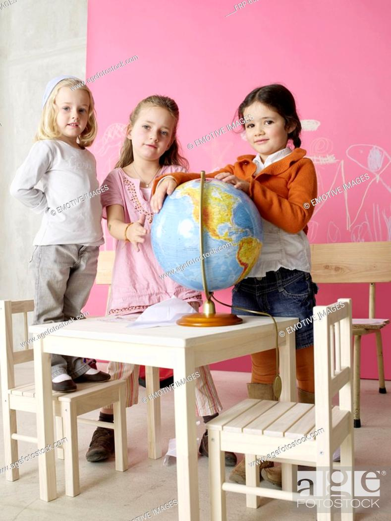 Stock Photo: Three girls with a globe.