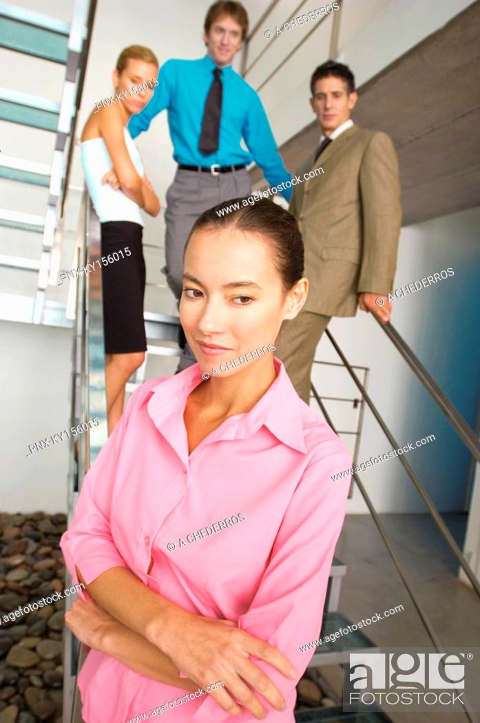 Stock Photo: Businesswoman standing with colleagues in background.