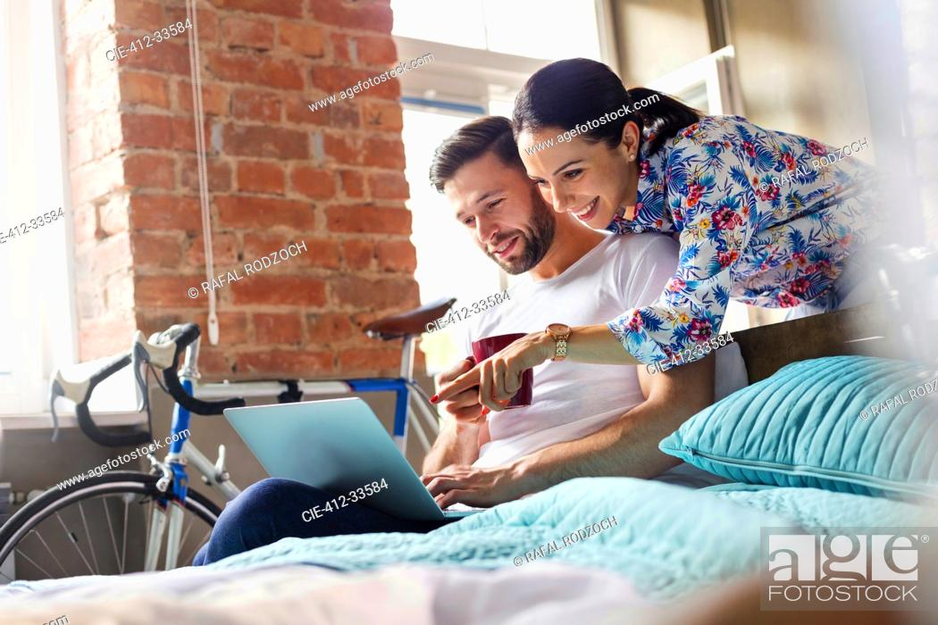 Stock Photo: Couple drinking coffee using laptop on bed.