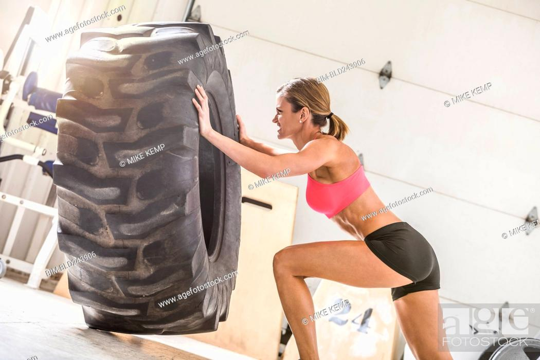Stock Photo: Woman pushing heavy tire in gymnasium.