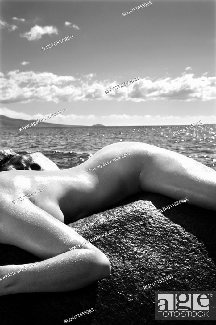 Stock Photo: Close up of nude woman draped over rock with coast in background.