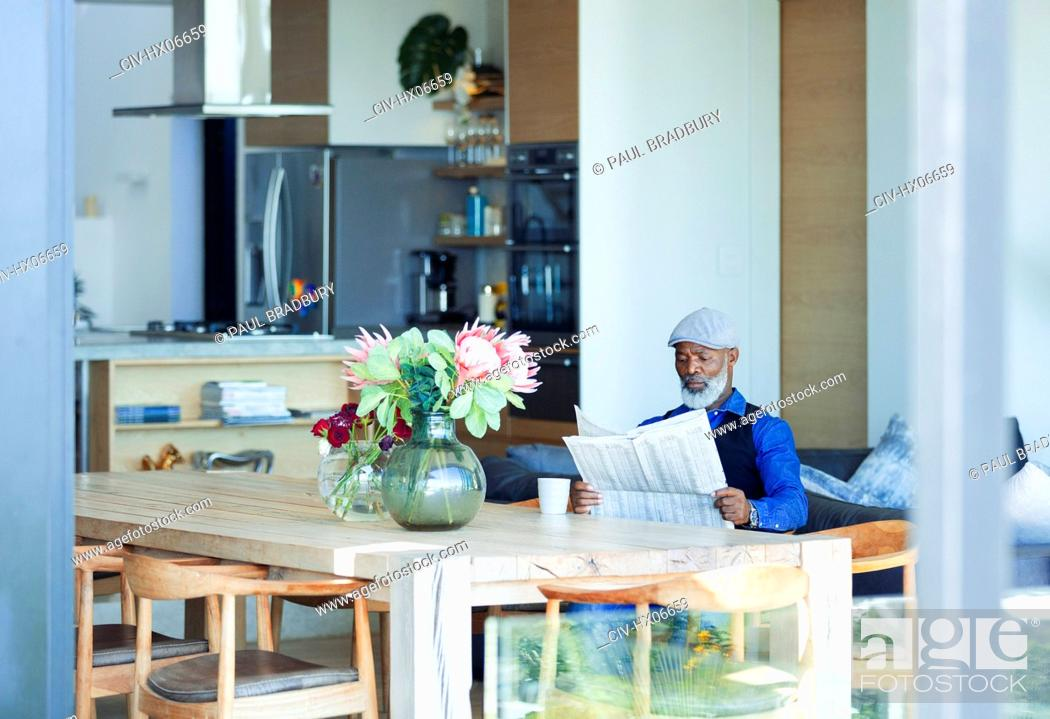 Stock Photo: Man reading newspaper and drinking coffee at dining table.