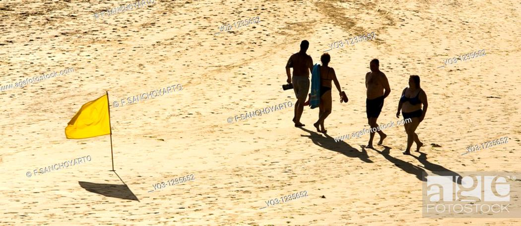 Stock Photo: Vacationers walking by a yellow flag. Oriñon Beach, Castro Urdiales, Cantabria, Spain.