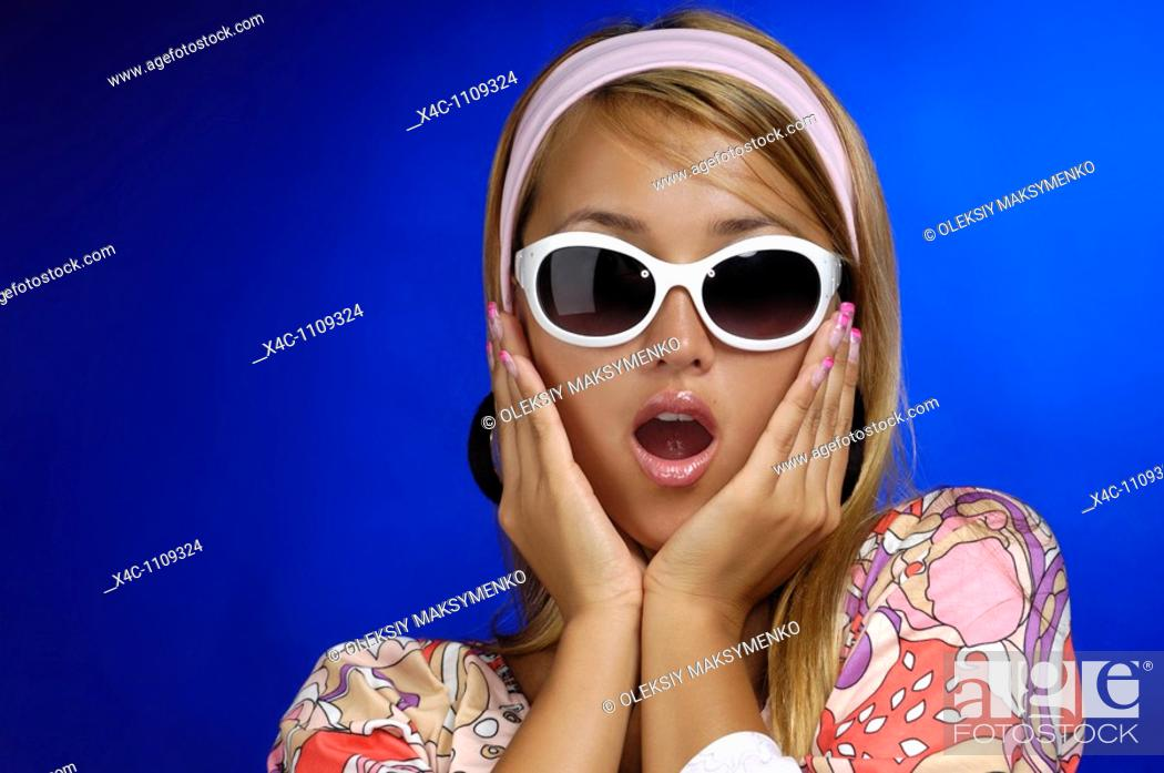 Stock Photo: Young fashionable woman in a fancy retro outfit with funny surprized expression. Conceptual closeup portrait. Isolated on blue background.