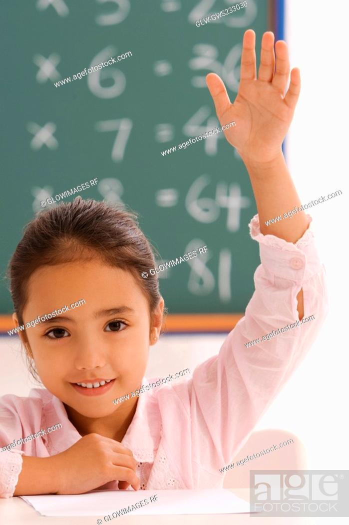 Stock Photo: Portrait of a schoolgirl with her hand raised in a classroom.