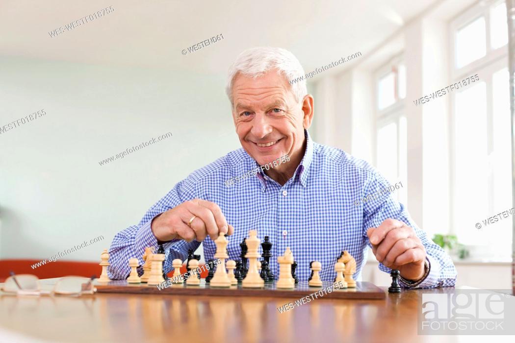 Stock Photo: Germany, Leipzig, Senior man playing chess game.