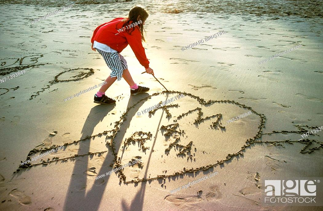 Stock Photo: Young girl draws a love heart in the sand at the beach as the sun fades into an evening glow.