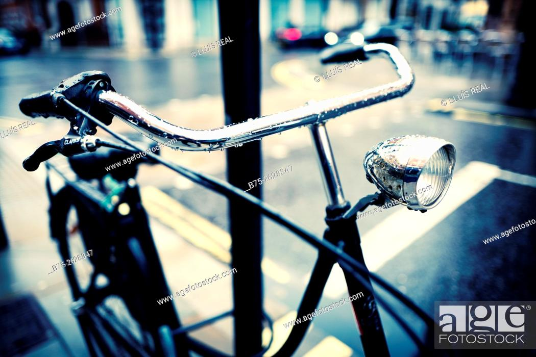 Stock Photo: Close-up of the handlebar and lamp of a Dutch bicycle parked on a lamppost, on a rainy day. London, England, UK, Europe.