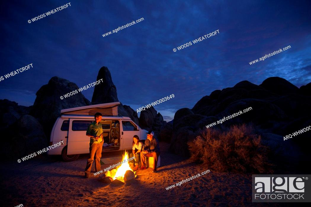 Stock Photo: Group of friends around campfire at night while camping in Alabama Hills Recreation Area, Lone Pine, California, USA.