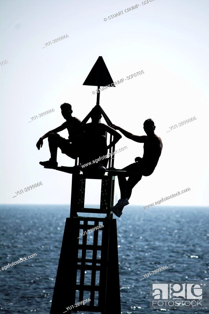 Stock Photo: Silhouette of three youths balance on a harbour marker at the entrance to cartagena harbour in Murcia Spain.