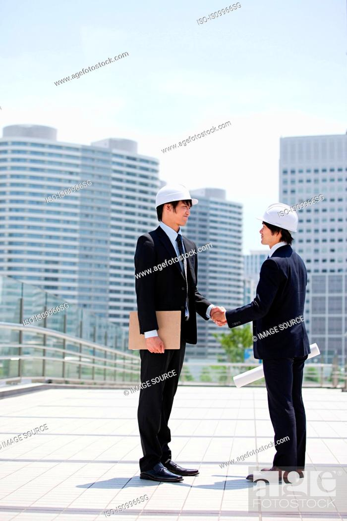 Stock Photo: Two businessmen wearing hard hats, shaking hands.