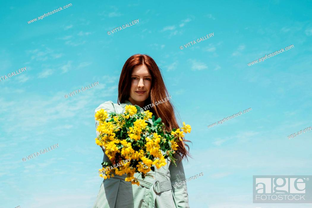 Stock Photo: Portrait of redheaded young woman against sky presenting bunch of yellow flowers.