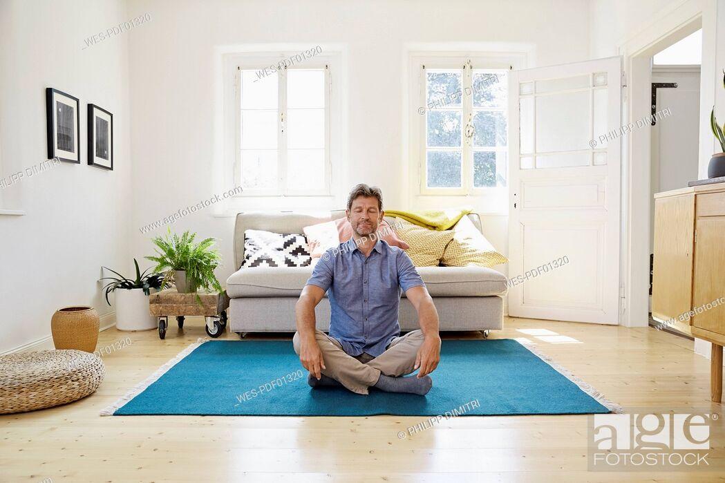 Stock Photo: Man sitting on ground, meditating.