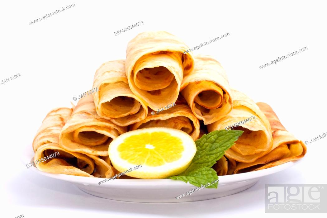 Stock Photo: Delicious rolled crepes with lemon and mint, isolated on white background.