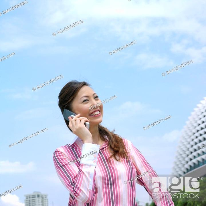 Stock Photo: Low angle view of a mid adult woman talking on a mobile phone.