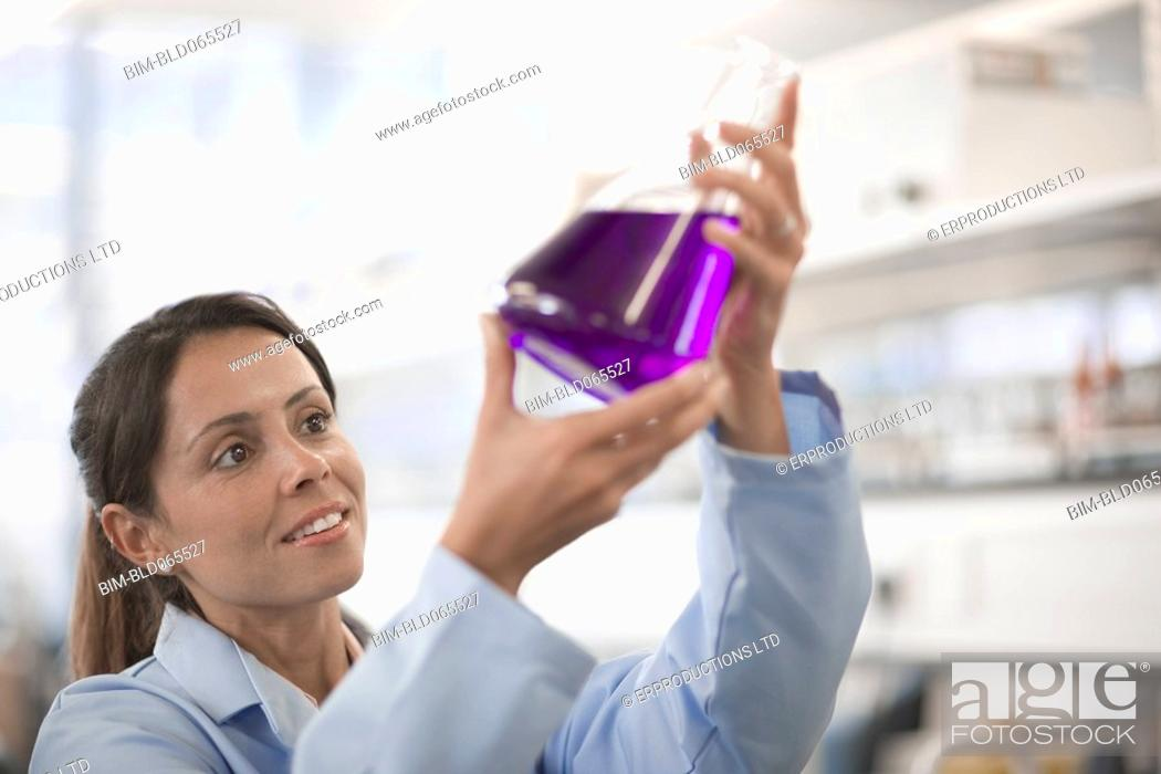 Stock Photo: Mixed race scientist working in laboratory with beaker of liquid.