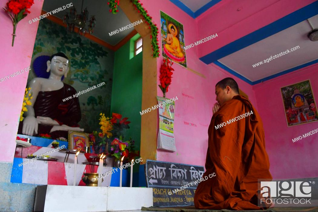 Imagen: AGARTALA, TRIPURA, INDIA, 07-05-2020 : A Monk , alone , is doing the rituals in a buddhist temple , as there will be no gathering of devotees on the occasion.