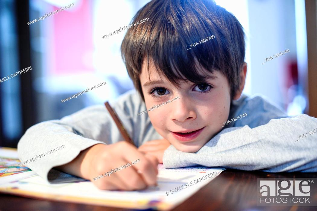 Stock Photo: child performs the duties on the table.