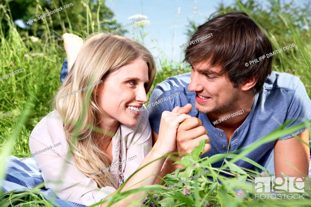 Stock Photo: Germany, Cologne, Young couple lying in meadow, smiling.