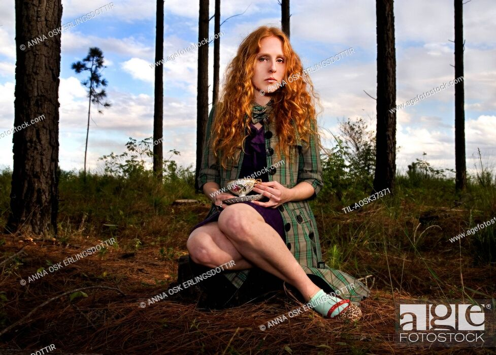Stock Photo: Lone female figure with long red hair sitting with a cup of tea in woodland.