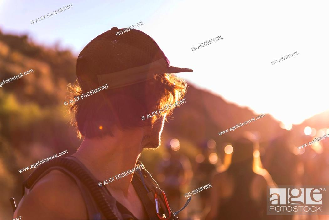 Stock Photo: Man in baseball cap looking over his shoulder at group of people, sunset.