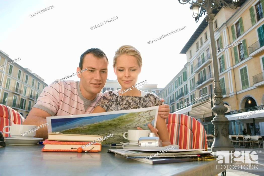 Stock Photo: Man and woman at outdoor cafe reading map.
