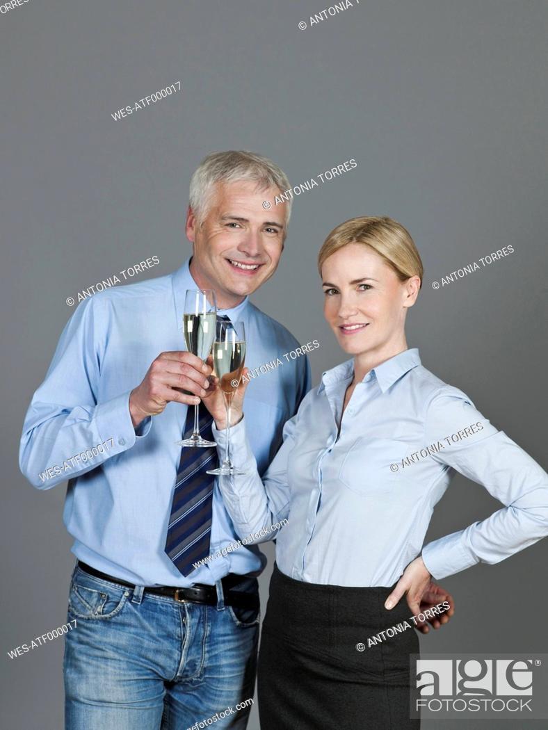 Stock Photo: Mature couple drinking sparkling wine, smiling, portrait.
