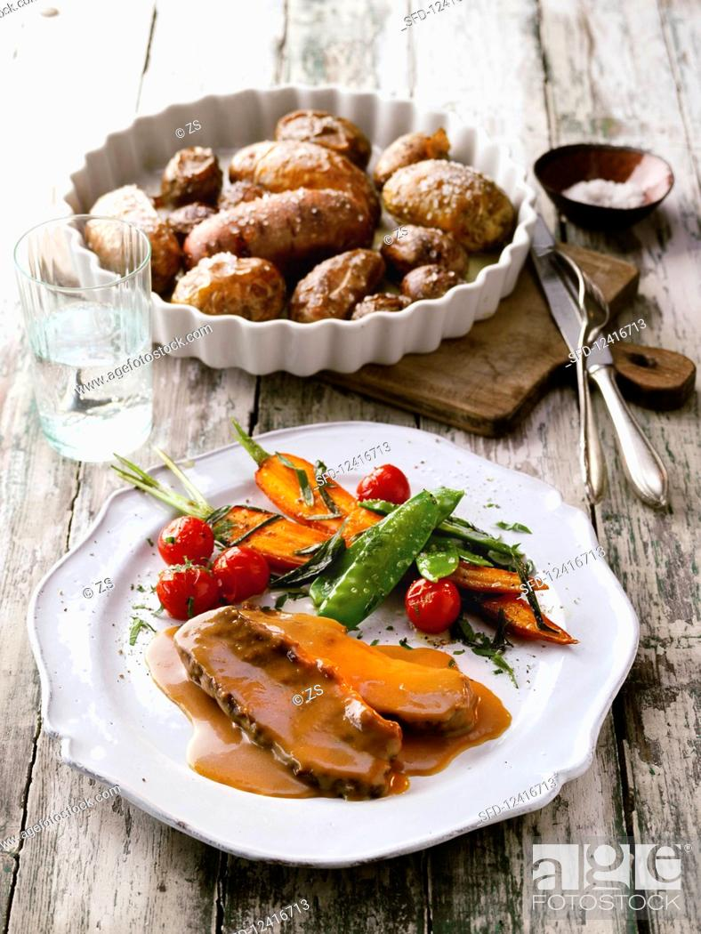 Stock Photo: Roast beef with colourful baked potatoes and young vegetables.