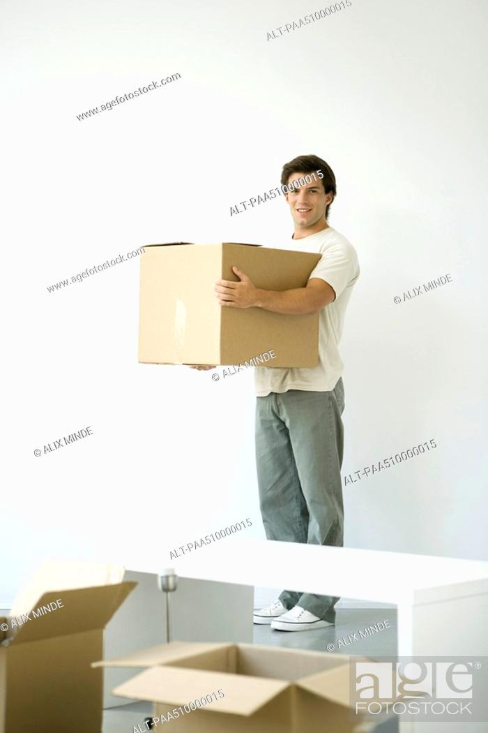 Stock Photo: Man holding cardboard box, smiling at camera, opened boxes in foreground.