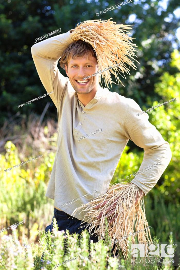 Stock Photo: Portrait of a man standing in a field as scarecrow.