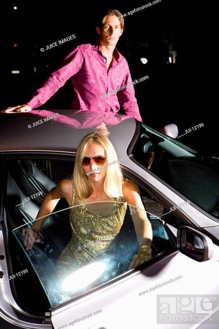 Stock Photo: Young couple alighting from car, portrait, night.